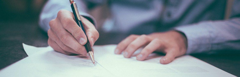 Person, die einen Vertrag unterschreibt